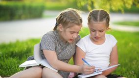 Girls doing homework in the summer garden. They are having a lot of fun getting knowledge. Happy, fun, hd, books, homework stock video
