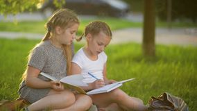 Girls doing homework in the summer garden. They are having a lot of fun getting knowledge. Happy, fun, hd, books, homework stock video footage