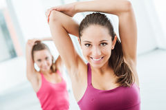 Girls doing stretching exercises at the gym. Young women at the gym sitting on a mat and doing stretching exercises for arms Royalty Free Stock Image