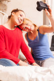 Girls doing themselves photo in a bedroom Stock Photos