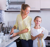 Girls doing and wiping dishes in kitchen Stock Image