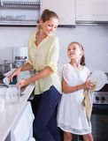 Girls doing and wiping dishes in kitchen Royalty Free Stock Images