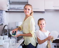 Girls doing and wiping dishes in kitchen Stock Photography