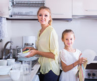 Girls doing and wiping dishes in kitchen Stock Images