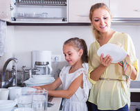 Girls doing and wiping dishes in kitchen Royalty Free Stock Photo
