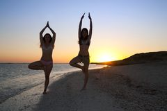 Girls doing yoga against sunset Stock Photos