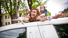 girls dragging bride in limousines hatch Royalty Free Stock Photography