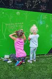 Girls drawing with chalk. Dnipro, Ukraine - June 27, 2018: Little girls draws funny scribbles on the day of putting into operation an inclusive city park stock photography
