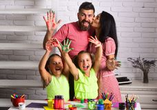 Girls drawing with colorful paints. Mother and father kissing with painted hands. Happy childhood and parenting. Family love and care concept. Arts and crafts stock image