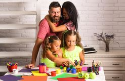 Girls drawing with colorful paints, markers and pencil on table. Woman hugging men on white wall. Family love and care concept. Happy childhood and parenting royalty free stock photography