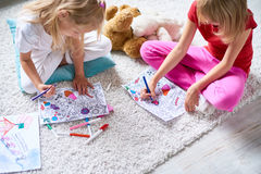 Girls Drawing in Coloring Books on Floor royalty free stock photos