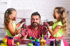 Girls drawing on man face skin with colorful paints Stock Photography