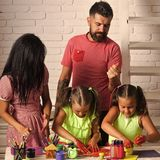 Girls drawing with mother and father. Happy childhood and parenting. Imagination, creativity concept. Finger painting. And arts. Children playing and learning Royalty Free Stock Image