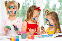 Girls drawing. Three little girls drawing with gouaches on paper Royalty Free Stock Photo