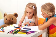 Girls drawing together - older sister helping the little one Royalty Free Stock Image