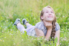Girls dream. Young happy girl lying on the green meadow and dreaming of something Stock Images