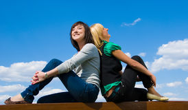 Girls dreams. Blonde and brunette sit back to back on the sky background and dream of something beautiful Royalty Free Stock Photos