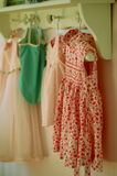 Girls dresses and bathing suit. Dresses and bathing suit hanging in a little girl's bedroom. Taken in natural light Stock Images