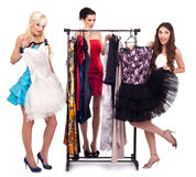 Girls in dresses boutique. Fashion girls choose dresses in boutique, isolated on white background royalty free stock images