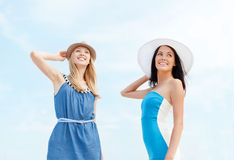 Girls in dresses with hats on the beach Stock Image