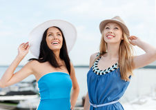 Girls in dresses with hats on the beach Royalty Free Stock Image