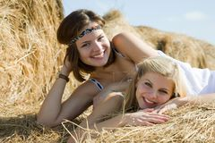 Girls in dresses resting on hay Royalty Free Stock Photos