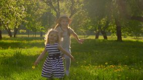 Girls in dresses running with a dog at sunset. Two wonderful girls in dresses running with a dog in the garden at sunset stock footage