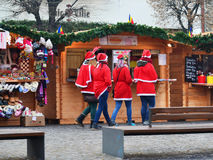 Girls dresses in Santa Claus costumes do shopping at the Christmas market Stock Photo