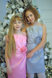 Girls in dresses sister at the Christmas tree on Christmas Royalty Free Stock Photography