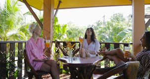 Girls Drink Juice Sit At Table Talking On Terrace In Tropical Forest, Women Group Morning. Slow Motion 60 stock video footage