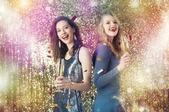 Girls drink sparkling wine to celebrate the new year. Happy girls drink sparkling wine to celebrate the new year royalty free stock photos