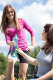 Girls drink water on bicycle trip Royalty Free Stock Images