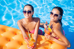 Girls drinking cocktails in swimming pool Stock Photos