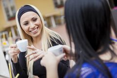 Girls drinking coffe in restaurant Stock Images