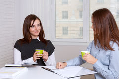 Girls drinking coffee while sitting at their desk Stock Images