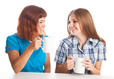 Girls are drinking from the cups Stock Images
