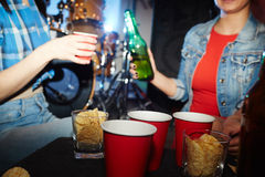 Girls Drinking at House Party. Mid section portrait of two modern girls drinking beer behind table with beer cups and snacks Royalty Free Stock Image