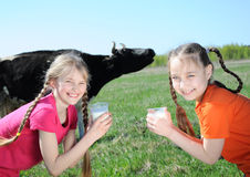 Girls drinking milk. Two happy little girls drinking milk at farm Royalty Free Stock Image