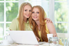 Girls  drinking tea   with laptop Royalty Free Stock Photography