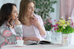 Girls  drinking tea  with magazine Stock Image