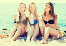 Girls drinking water on beach Royalty Free Stock Photo
