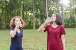 Girls drinking water after excercise. Two Asian girls drinking water from bottle after excercise Royalty Free Stock Photos