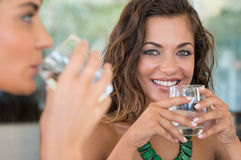 Girls Drinking Water. Two Female Friends Drinking Mineral Water With Glass At Bar Royalty Free Stock Image