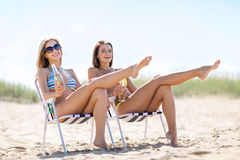 Girls with drinks on the beach chairs. Summer holidays and vacation - girls in bikinis with drinks on the beach chairs Stock Images