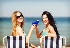 Girls with drinks on the beach chairs Royalty Free Stock Images
