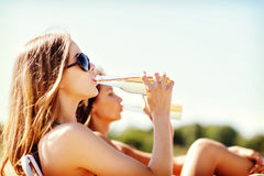 Girls with drinks on the beach chairs Royalty Free Stock Photos