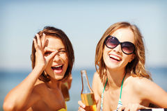 Girls with drinks on the beach chairs Stock Image