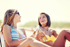 Girls with drinks on the beach chairs Royalty Free Stock Image