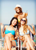 Girls with drinks on the beach chairs Stock Photos