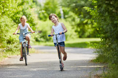 Girls drive scooter and ride bike. In the park during summer vacation Royalty Free Stock Image